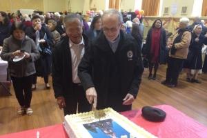 Fr Brian McCoy cuts the anniversary cake.